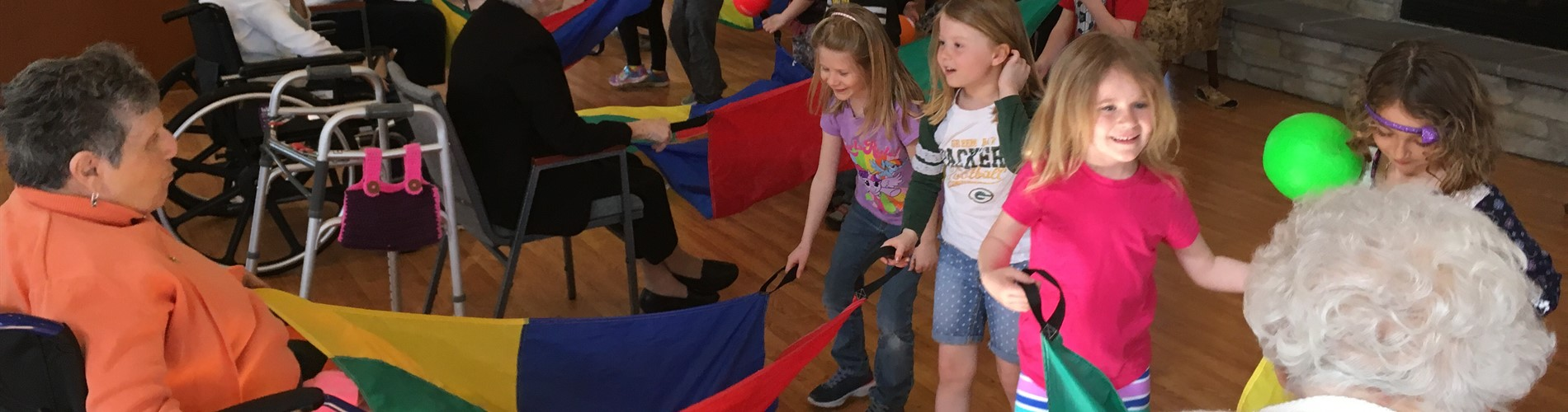 Junior Kindergartners go to Cedar Bay to play parachutes with the residents.